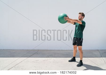 Medicine ball workout fitness man strength training arms doing deltoid front raise exercise for shoulder muscles. Upper body workout with weight ball at fitness centre.