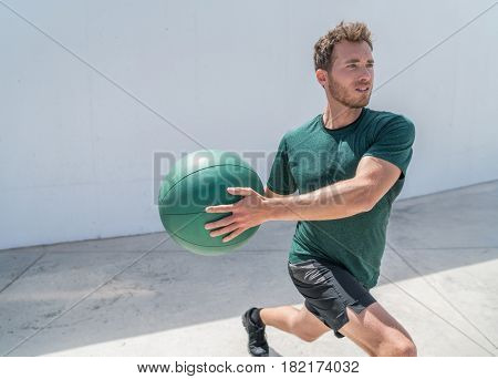 Man exercising with medicine ball at fitness centre. Gym workout strength training person working out doing lunges twist for core workout with medicine ball weight.