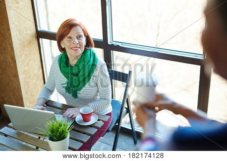 Senior female talking to her buddy in cafe while browsing in the net