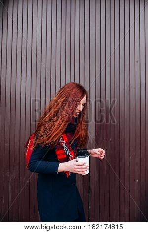 Beautiful hipster fashion model with red hair and coffee posing in front of the wall outdoor