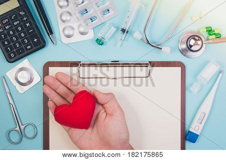 Topview Of Hands Holding Red Heart Over Paper Board For Health Care Concept With Pen, Medicine, Calc