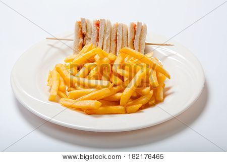 Club Sandwiches With Chicken And French Fries On A White Plate