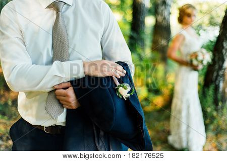 Groom is holding a jacket with a buttonhole on his hand with bride in blur on background. Man holding suit jacket over his hand