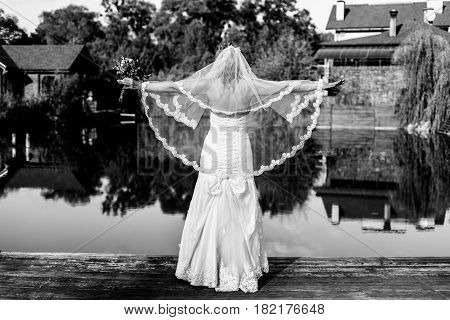 Happy bride in a wedding dress and veil with a bouquet in her hands is standing near the lake with her arms outstretched. Black and white photography