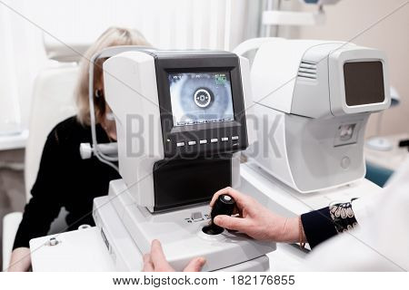 Women looking at eye test machine in ophthalmology clinic.