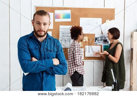 Successful businessman smiling, posing with crossed arms. Colleagues discussing new ideas background.