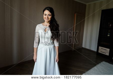 Beautiful young bride in white dress waiting for the groom indoors. Elegant charming young brunette bride is posing indoors in a wedding dress. Morning the bride