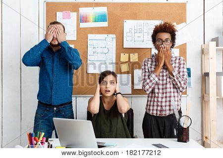 Colleagues closing mouth, eyes and ears with hands in office.