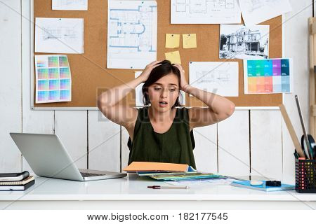 Upset young beautiful businesswoman holding hands on head, sitting at workplace in office.