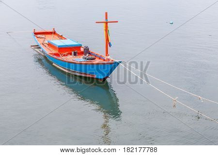 Blue and red vacant fisherman's rowboat floating on sea traditional fishing in Thailand.