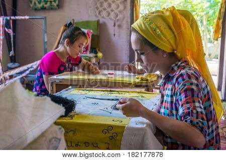 Woman Embroidering Fabric