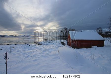 Wonderfull Norwegian landscape during wintertime with a nice red colored storehouse in front