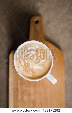 Delicious coffee in white mug on wooden background