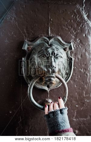 Hand holding metal lion door knocker on a wooden door