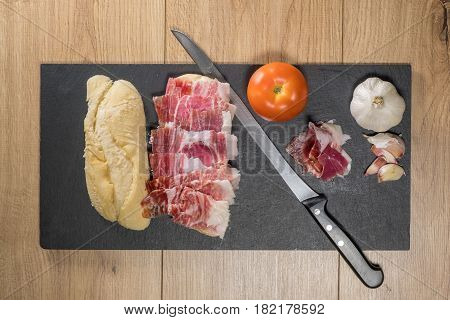 Iberian Acorn Ham Sandwich over a slate stone with tomato, garlic bulb and knife
