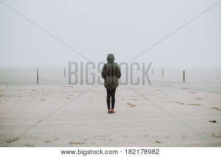 Woman standing on the empty beach in winter