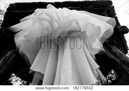 Bottom view of wedding dress hanging on the arbor. Abstract overhang wedding dress