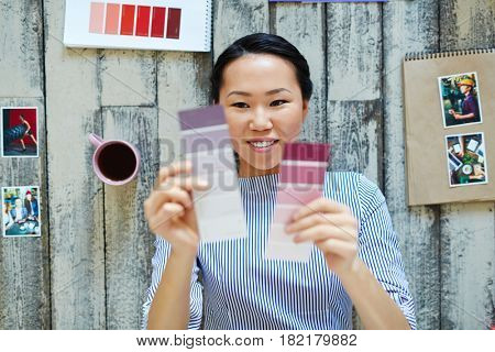 Young designer choosing between lilac and purple color swatches