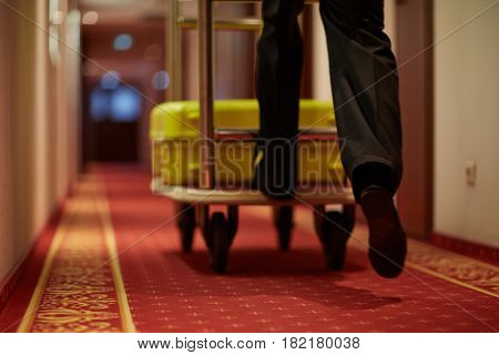 Porter moving luggage in cart down aisle covered by red carpet
