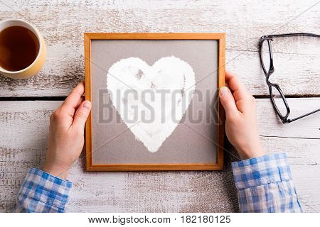 Mothers day composition. Hands of unrecognizable woman holding picture frame with heart. Eyeglasses and cup of tea laid on table. Studio shot on white wooden background. Flat lay.