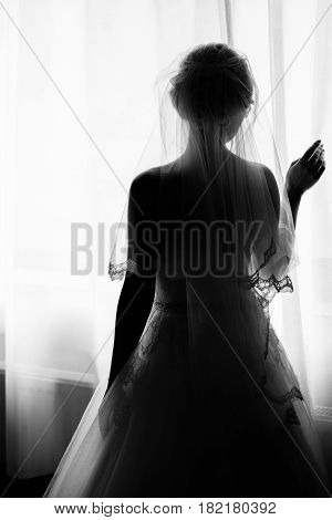 Silhouette of beautiful bride is standing at the window and holding curtains. Morning of the bride. Bride in veil posing in sunlight at window in morning. Getting ready. Black and white photo