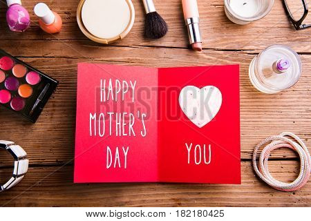 Mothers day composition. Red greeting card and various beauty products laid on table. Studio shot on wooden background. Flat lay.