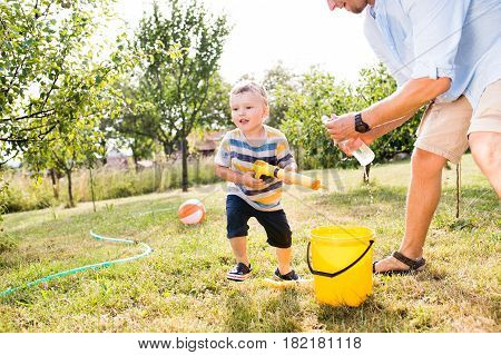 Little boy with unrecognizable father playing with water guns, splashing, fun in garden, sunny summer day, back yard
