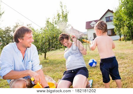 Little boy with mother and father splashing each other, fun in garden, sunny summer day, back yard