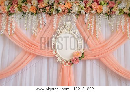 Place for newlyweds decorated with flowers and peach cloth with an empty wedding frame for names of the bride and groom. Floral wedding decorations. Blank card for the bride's and groom's names