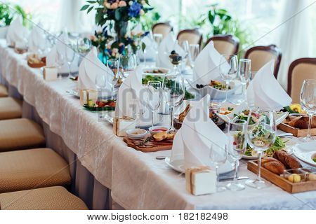 Table setting. Table served for wedding banquet close up view. White napkin on a white empty plate on a dining table