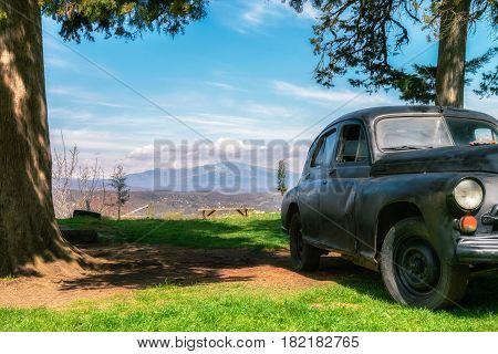 Georgia, Kutaisi - April 01, 2017: Old car in Gelati is a medieval monastic complex near Kutaisi. Gelati was founded in 1106 by King David IV and is recognized by UNESCO as a World Heritage Site.