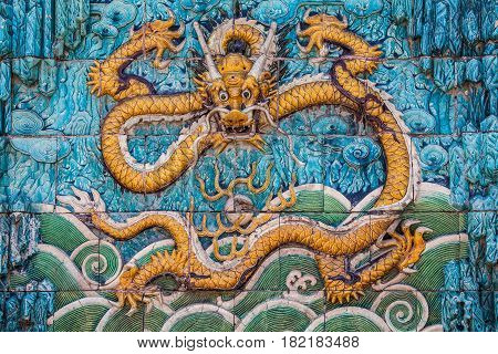 Central yellow dragon with raised forepaws, clouds and waves on the nine dragon wall in the Forbidden city in Beijing