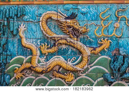 Golden scaled imperial dragon with white crest floating in green stormy waves on the nine dragon wall in the Forbidden City in Beijing