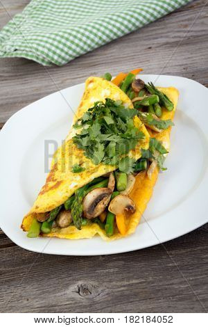 Stuffed vegetable omelet with asparagus pepper and mushroom on wooden background with cilantro on top
