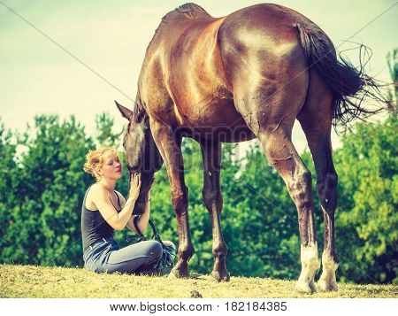 Jockey Woman Sitting With Horse On Meadow