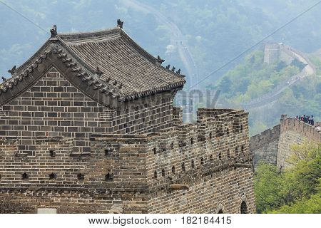 Big watchtower of the Great Wall of China with traditional tile roof decorated animal figures and ornamental eaves