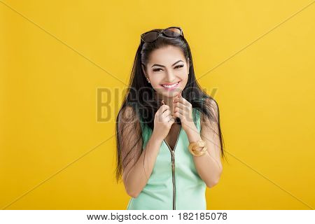 attractive young brunette woman in a green swimsuit on a yellow background. smilling girl in a turquoise bodysuit