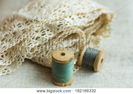 Vintage wood spools with green and grey threads on linen fabric cotton lace swing hobby concept copyspace website banner