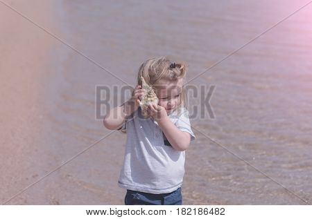 small little child with blond hair listening to seashell or marine shell cute baby boy on sea beach with crystal clear water on sunny day on rosy seascape background. Idyllic summer vacation