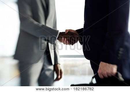 Midsection of two partners greeting one another after making deal