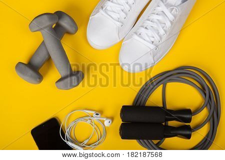 Sport shoes dumbbells mobile phone and skipping rope on yellow background. Top view. Fitness sport and healthy lifestyle concept.