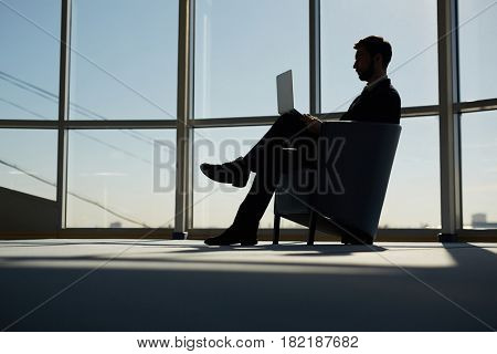 Analyst or banker with laptop looking through online data