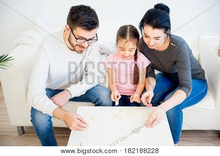 Cheerful family of three playing domino at home