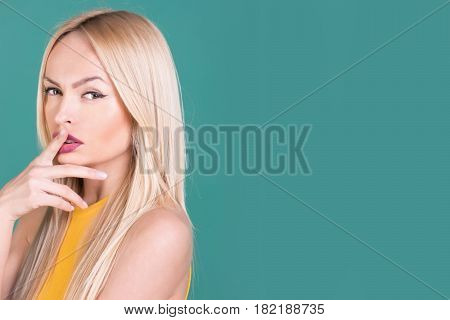Young skin stylish makeup and blond long hair hairstyle. Pretty woman or cute girl with fingers at sexy lips mouth on blue background. Beauty skincare and hairdressing copy space