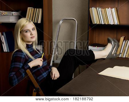 young female librarian reading a big book in library. bookshelves with books, stepladder and desk with lamp.