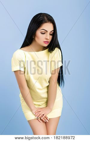 shy young brunette woman adjusts her yellow dress on the blue background.