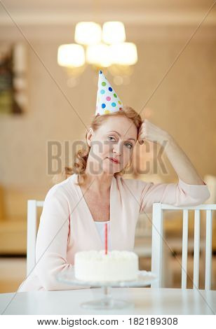 Offended female in birthday cap sitting on chair by table