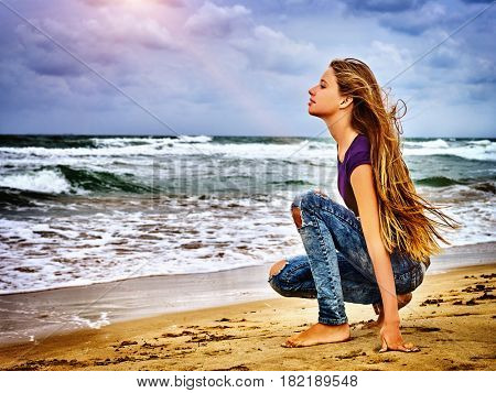 Girl on in sand beach looks thoughtfully into distance to last ray of sunset, falling on hectic sea. Art photography was taken in spring or summer. Woman in love .