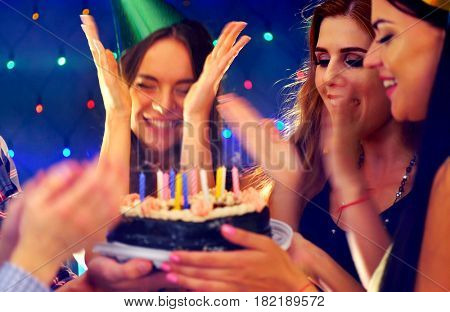 Happy friends birthday party with candle celebration cakes. Three girl joyfully clapping. Small group people looking at burning many candles in night spot. Women have fun hen-party on dark background.