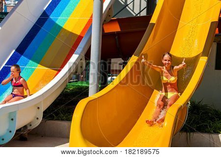Swimming pool slides for children on blue water slide at aquapark . Summer kids ride holiday outdoor. Happy beautiful sisters girl in two-piece swimsuit with hands up in aqua park. Good weather.